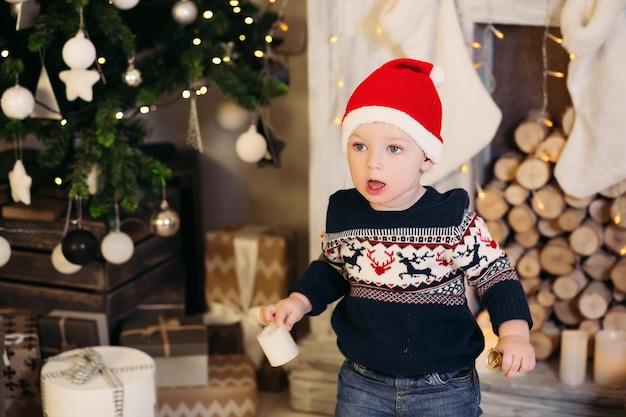 Portret van kleine blonde jongen zittend op het dak in ingerichte studio en spelen met kerstcadeautjes en dozen