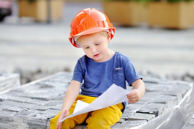 Portret van kleine bouwer in bouwvakkers die bouwtekening lezen.