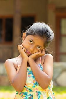 Portret van kleine brunette meisje met haar handen op haar gezicht