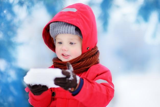 Portret van kleine grappige jongen in rode winterkleren met plezier met stuk ijs. actieve openluchtvrije tijd met kinderen in de winter. jong geitje met warme hoed, handhandschoenen en sjaal