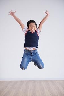 Portret van kleine jongen die gelukkig hoog in de lucht springt
