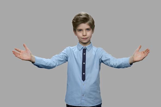 Portret van kleine jongen die handen op grijze achtergrond uitspreidt. leuke kindjongen die handen spreidt die iemand verwelkomen of begroeten.