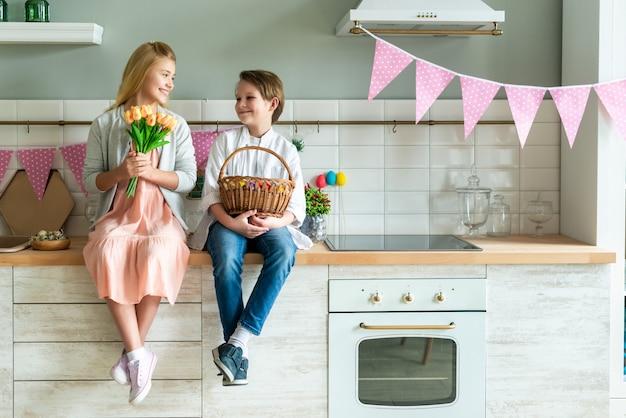 Portret van kleine jongen en meisje zitten in de keuken. ze houden een mand met paaseieren en een boeket tulpen
