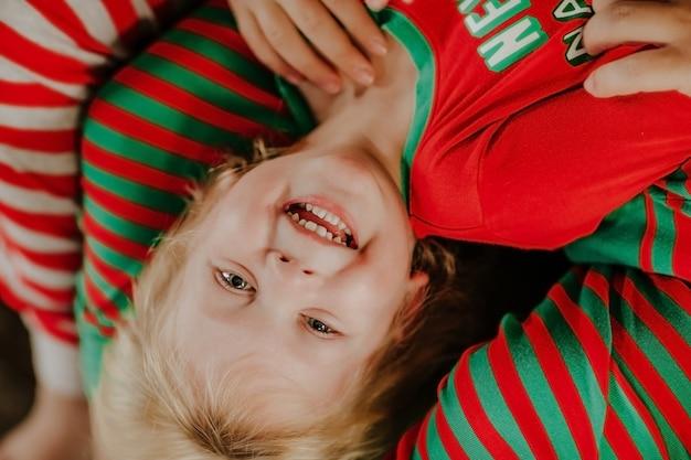 Portret van kleine jongen in rode en groene kerst pyjama neerhangend en lough vanwege kietelen.