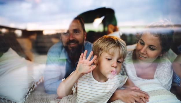 Portret van kleine jongen met ouders bij raam, vakantie in de natuur concept. door glas geschoten.