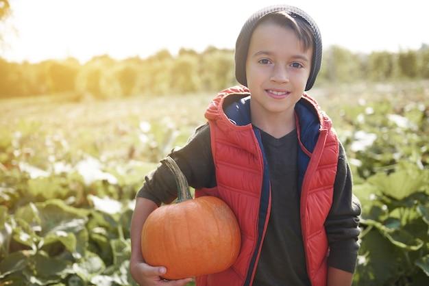 Portret van kleine jongen met rijpe pompoen