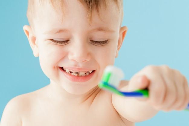 Portret van kleine jongen met tandenborstel op blauw.