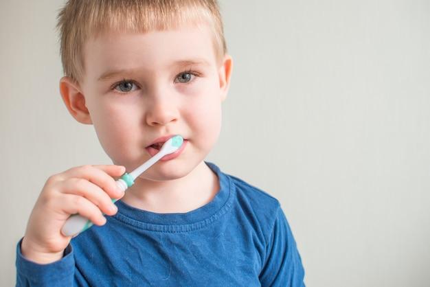 Portret van kleine jongen tandenpoetsen op lichte ruimte. mondhygiëne. kopieer ruimte voor tekst