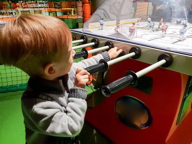 Portret van kleine peuterjongen die in tafelhockey speelt