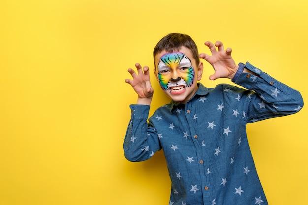 Portret van kleine schattige jongen met faceart op verjaardagsfeestje, schattige kleurrijke tijger geïsoleerd op gele muur.