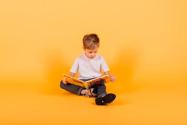 Portret van kleine schooljongen met boek op gele achtergrond, studio