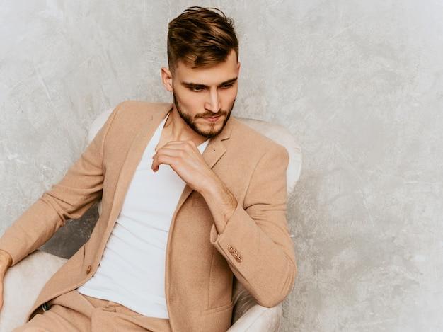 Portret van knap het glimlachen hipster zakenmanmodel die toevallig beige kostuum dragen. zittend in een stoel in interieur