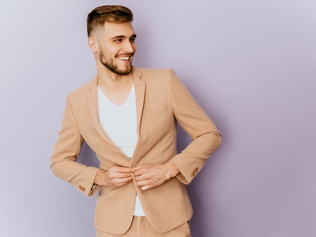 Portret van knap het glimlachen hipster zakenmanmodel die toevallig beige kostuum dragen.