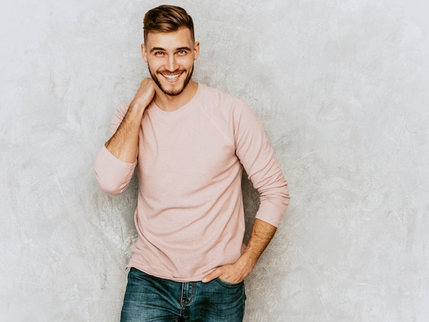 Portret van knap het glimlachen jonge mensenmodel die toevallige de zomer roze kleren dragen. mode stijlvolle man die zich voordeed