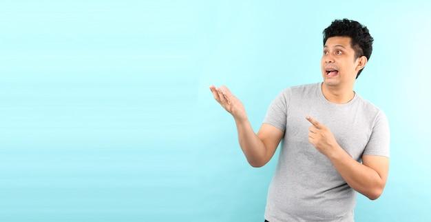 Portret van knap, schok en verrassingsgezicht van de aziatische mens die vinger op lege ruimte richten die op blauwe muur wordt geïsoleerd.