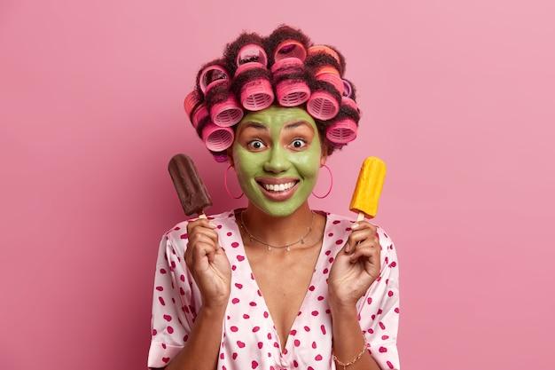 Portret van knap vrouwelijk model past groen schoonheidsmasker toe op het gezicht, draagt haarkrulspelden voor het maken van krullen, houdt chocolade en mango-ijs vast, heeft een gelukkig humeur, glimlacht breed, geïsoleerd op roze