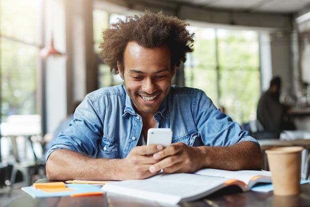 Portret van knappe afrikaanse donkere mannelijke student die smartphone bericht aan het typen houdt