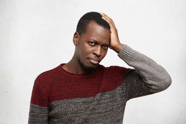 Portret van knappe afro-amerikaanse jonge man gekleed in warme casual trui