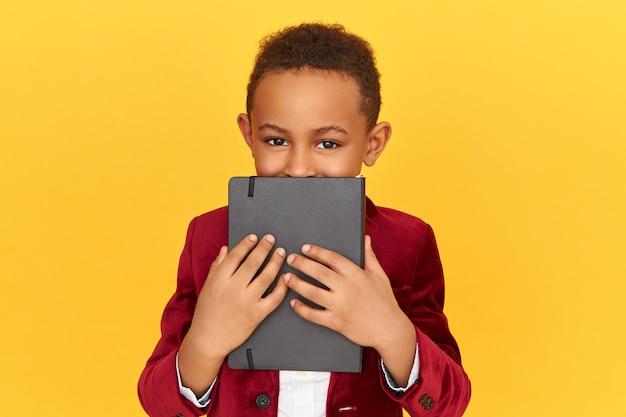 Portret van knappe afro amerikaanse jongen die speelse ogen heeft die gezicht behandelen met zwart exemplaarboek. zwarte leerling poseren geïsoleerd bedrijf dagboek, geheim houden