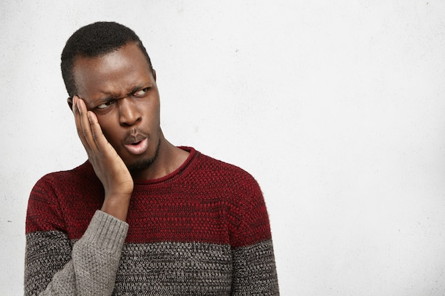 Portret van knappe afro-amerikaanse mannelijke student of klant fronsen, zijwaarts op zoek met geschokte of verbaasde uitdrukking, met hand op gezicht. donkere man met kiespijn, wang aan te raken