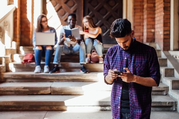 Portret van knappe, afro-amerikaanse student die naar mobiel kijkt