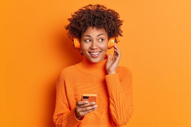 Portret van knappe afro-amerikaanse vrouw met krullend haar glimlacht heeft over het algemeen perfecte witte tanden