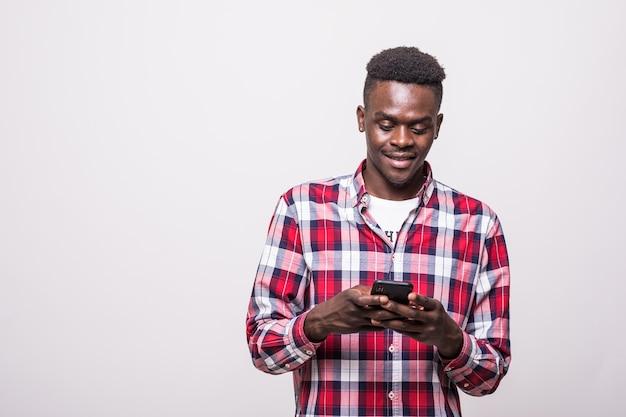 Portret van knappe afro man berichten verzenden en krijgen van zijn geliefde geïsoleerd