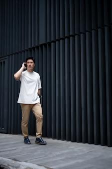 Portret van knappe aziatische man die smartphone buiten in de stad gebruikt