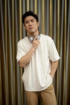 Portret van knappe aziatische man met koptelefoon buitenshuis
