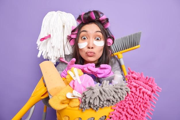 Portret van knappe aziatische vrouw stuurt airkis heeft verbaasde uitdrukking draagt haarrollers poses in de buurt van wasmand met schoonmaakgereedschap geïsoleerd over paarse muur