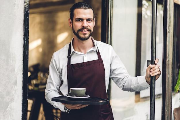Portret van knappe bebaarde barista man kleine ondernemer glimlachend en kopje koffie buiten het café of de coffeeshop houden. mannelijke barista permanent in café