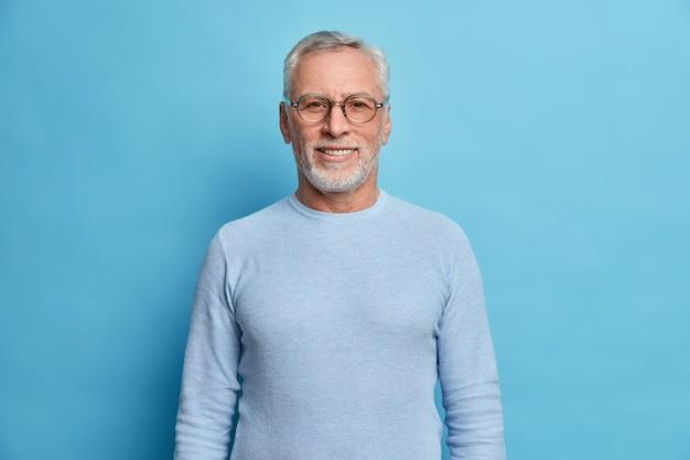 Portret van knappe bebaarde europese man met grijs haar en baard glimlacht aangenaam kijkt direct naar voorzijde in goed humeur heeft geluksdag draagt bril en trui geïsoleerd over blauwe muur
