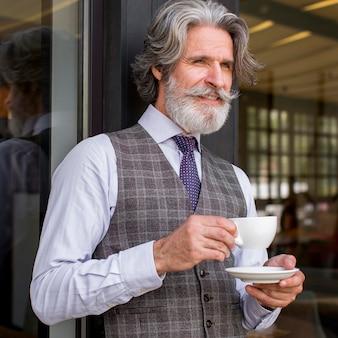 Portret van knappe bebaarde man die van koffie geniet