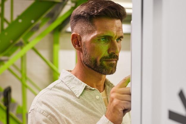 Portret van knappe bebaarde man met behulp van het configuratiescherm tijdens het gebruik van self storage unit, kopieer ruimte
