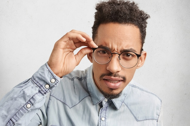 Portret van knappe bebaarde mannelijke student nerd draagt ronde bril, kijkt aandachtig