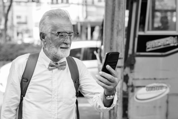 Portret van knappe bebaarde senior toeristische man stijlvolle kleding dragen tijdens het verkennen van de stad bangkok in zwart-wit