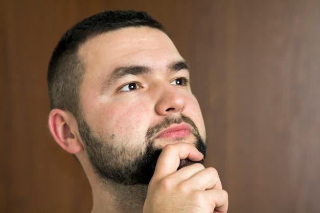 Portret van knappe bebaarde zelfverzekerde intelligente moderne fotogenieke jongeman met kort kapsel en zwarte ogen bedachtzaam vooruit kijken op onscherpe achtergrond.