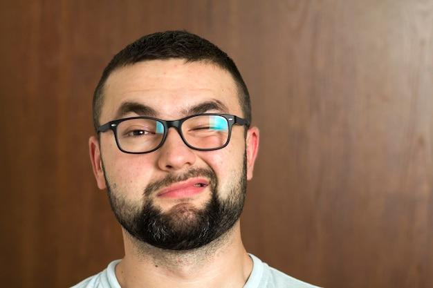 Portret van knappe bebaarde zwartharige intelligente moderne jongeman in glazen met kort kapsel en vriendelijke zwarte ogen glimlachend op onscherpe achtergrond.