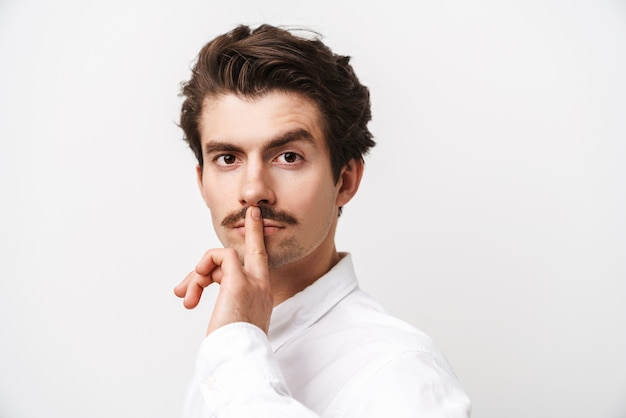 Portret van knappe besnorde man met shirt met vinger op zijn lippen geïsoleerd op wit