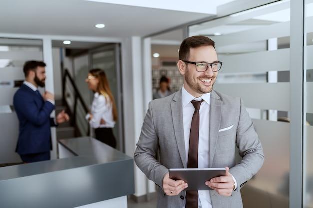Portret van knappe blanke glimlachende ongeschoren zakenman in pak en met bril staan in hal met tablet in handen.