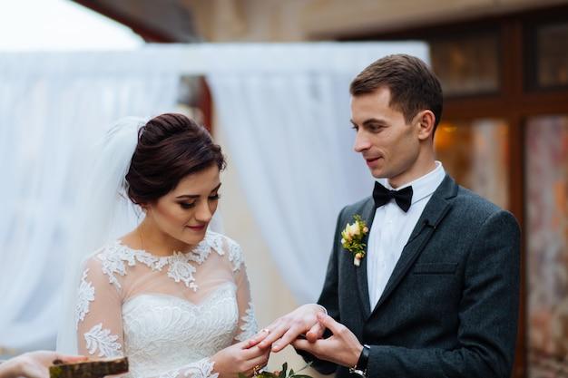Portret van knappe bruidegom die trouwring op bruidenhand zetten op registratiekantoor