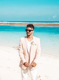 Portret van knappe bruidegom in het roze kostuum stellen op het strand achter blauwe hemel en oceaan