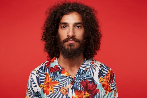 Portret van knappe bruinogige jonge bebaarde man met donker krullend haar kijken met kalm gezicht en houden zijn lippen gevouwen, geïsoleerd in vrijetijdskleding