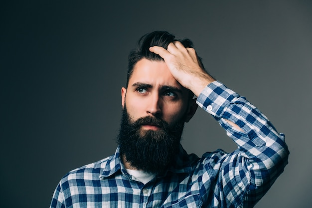 Portret van knappe denkende jonge man geïsoleerd op een grijze muur