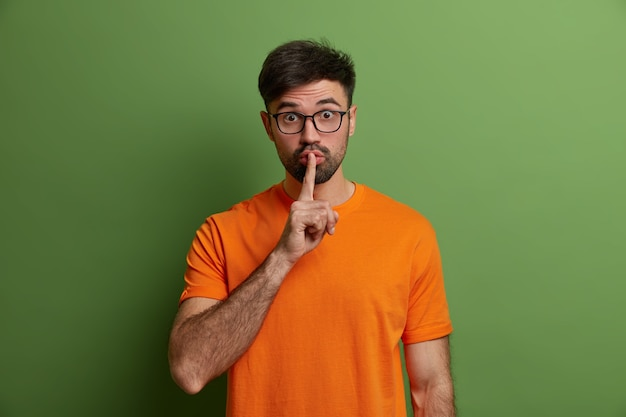 Portret van knappe donkerbruine man maakt stilte gebaar, houdt wijsvinger op de lippen, heeft een geheim plan, verrast zoals geruchten vertelt, draagt een transparante bril, verbergt geheim, poseert over groene muur