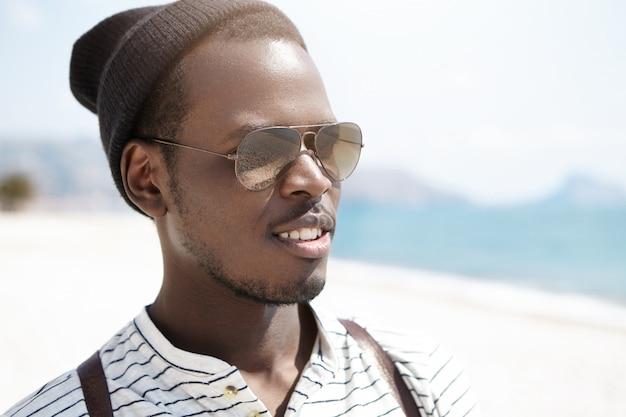 Portret van knappe donkere hipster in gespiegelde tinten en stijlvolle hoed, op afstand kijken met tas op zijn schouders