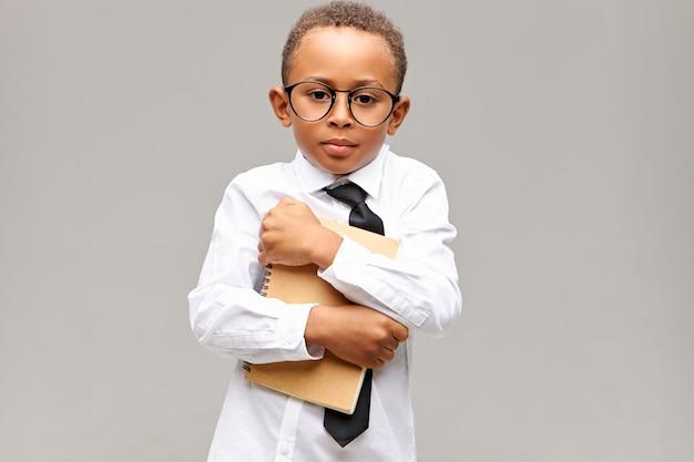 Portret van knappe donkere schooljongen met korte afro-kapsel poseren geïsoleerd in glazen, overhemd en stropdas omarmen voorbeeldenboek, verlegen in de nieuwe school. leren en kennis