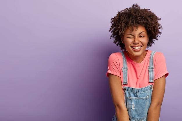 Portret van knappe donkerhuidige vrouw met krullend kapsel, knipperend oog, heeft plezier, lacht aangenaam, gekleed in stijlvolle kleding, drukt gelukkige emoties uit, geïsoleerd op paarse achtergrond, kopie ruimte