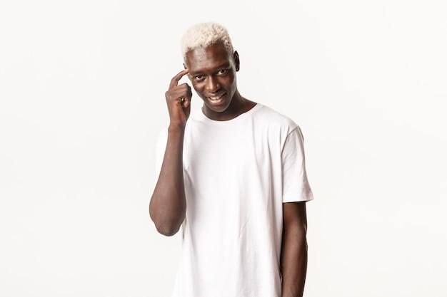 Portret van knappe doordachte afro-amerikaanse blonde man, met zelfvoldane gezicht, glimlachend sluw en wijzend naar het hoofd, vraagend om na te denken