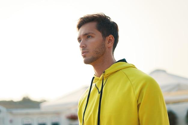 Portret van knappe doordachte man in gele hoodie